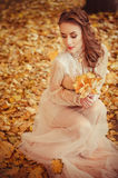 Portrait of a beautiful young girl with blue eyes and braided hair and a bouquet of autumn leaves in the hands, a gentle long dres Stock Photo