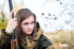 Portrait of a beautiful young girl in camouflage hunter with shotgun. Portrait of a beautiful girl in white camouflage hunter with a gun on a background of Royalty Free Stock Photography