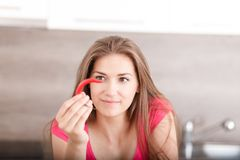Portrait of a beautiful young girl with chili pepper. Stock Photo
