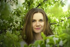 Portrait of beautiful young girl close up among a blossoming tree with green leaves outdoors Royalty Free Stock Photos