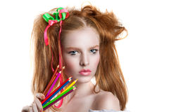 Portrait of a beautiful young girl with colored pencils in hand. Girl with creative hairstyle and makeup holding pencils. Royalty Free Stock Images