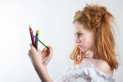 Portrait of a beautiful young girl with colored pencils in hand. Girl with creative hairstyle and makeup holding pencils. Royalty Free Stock Image