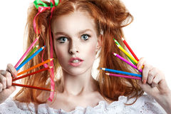 Portrait of a beautiful young girl with colored pencils in hand. Girl with creative hairstyle and makeup holding pencils. Royalty Free Stock Photos