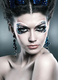Portrait of a beautiful young girl with colourful cosmetics and a fashionable hairstyle Royalty Free Stock Photo