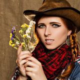 Portrait of a beautiful young girl in a cowboy hat with wild dried flowers Royalty Free Stock Images