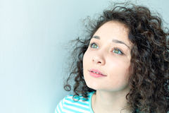 Portrait of a beautiful young girl with curly hair. Big green eyes and eyelashes closeup. Lookup Royalty Free Stock Photo
