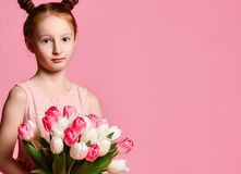 Portrait of a beautiful young girl in dress holding big bouquet of irises and tulips isolated over pink background royalty free stock images
