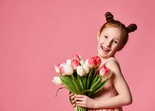 Portrait of a beautiful young girl in dress holding big bouquet of irises and tulips isolated over pink background royalty free stock photo