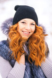 Portrait of beautiful young girl dressed in fur coat at winter b Stock Photos