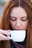 Portrait  of a beautiful young girl drinking coffee outdoors loo Stock Image