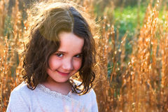 Portrait of beautiful young girl in field smiling. Lovely young girl looking at camera smiling on a sunny day with beautiful bokeh background Royalty Free Stock Photo