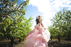 Portrait of a beautiful young girl in a flying bride tender pink dress on a background of green field, she laughs and poses with a Stock Photo