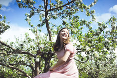 Portrait of a beautiful young girl in a flying bride tender pink dress on a background of green field, she laughs and poses with a Royalty Free Stock Images