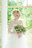 Portrait of beautiful young girl in the garden. Beautiful blonde bride in a luxurious dress with wedding bouquet Stock Photography