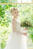 Portrait of beautiful young girl in the garden. Beautiful blonde bride in a luxurious dress with wedding bouquet Royalty Free Stock Photo