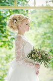 Portrait of beautiful young girl in the garden. Beautiful blonde bride in a luxurious dress with wedding bouquet Royalty Free Stock Photos