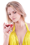 Portrait of beautiful young girl with a glass of champagne. Isol. Rubs a young girl in a yellow dress with a glass of red champagne in hand isolated on white Stock Images