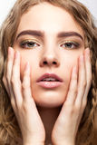 Portrait of beautiful young girl with hands on the face. Royalty Free Stock Photo