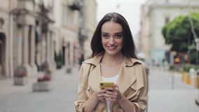 Portrait of Beautiful Young Girl Holding Mobile Phone Chatting Standing Loking into Camera and Smiling at City. Background stock video footage