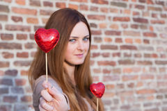 Portrait of a  beautiful young girl holding two hearts. One next to her chest and handing another Royalty Free Stock Image