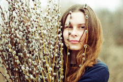 Portrait of a beautiful young girl with a huge armful of willow Stock Image