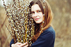 Portrait of a beautiful young girl with a huge armful of willow Royalty Free Stock Image