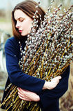 Portrait of a beautiful young girl with a huge armful of willow Stock Images