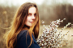 Portrait of a beautiful young girl with a huge armful of willow Royalty Free Stock Photo