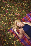 Portrait of a beautiful young girl lays in autumn Stock Images