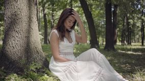 Portrait beautiful young girl with long brunette hair wearing a long white summer fashion dress sitting under a tree in stock video