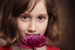 Portrait of a beautiful young girl looking at the camera. A beautiful young girl holding a pink flower and looking at the camera Royalty Free Stock Images