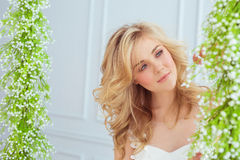 Portrait of beautiful young girl looks to the flowers. Portrait of a beautiful young girl looks to the flowers Royalty Free Stock Photography