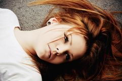 Portrait of beautiful young girl lying on asphalt Royalty Free Stock Photography