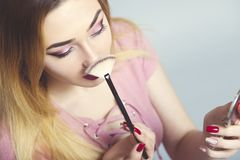 Portrait of a beautiful young girl with makeup brush in a studio, woman face, cosmetics and natural beauty concept royalty free stock photos