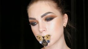 Portrait of a beautiful young girl model with fashionable smoky eyes makeup and a butterfly on her lips posing in front