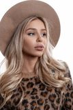 Portrait of a beautiful young girl with natural make-up with lips with long curly blond hair in an elegant hat. In a fashionable leopard sweater on a white stock photography