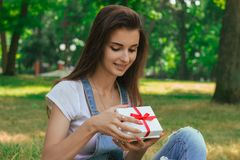 Portrait of beautiful young girl opens a gift with red ribbon. At the park Royalty Free Stock Image
