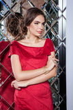 Portrait of a beautiful young girl in a red dress on a backgroun Royalty Free Stock Images
