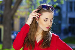 Portrait of a beautiful young girl in red shirt on the backgroun Stock Photos