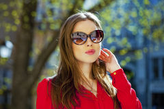 Portrait of a beautiful young girl in red shirt on the backgroun Stock Images