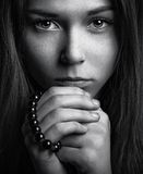 Portrait of a beautiful young girl with a rosary in his hands Royalty Free Stock Image