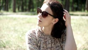 Portrait of beautiful young girl sitting on grass in sunglasses stock video footage