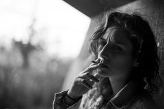 Portrait of beautiful young girl smoking a cigarette on urban ba Royalty Free Stock Image