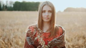 Portrait of beautiful young girl standing at a wheat field looking at camera in the sunset light. Modern farming, happy stock footage