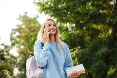 Portrait of a beautiful young girl student with backpack. And textbook walking at the park, talking on mobile phone Stock Images