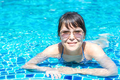 Portrait of a beautiful young girl in sunglasses floating in the Stock Photos