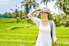 Portrait of beautiful young girl traveler in hat, glasses, with backpack looks into the distance on the rice field, Bali Indonesia