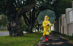 Little girl in raincoat walking with umbrella royalty free stock photos