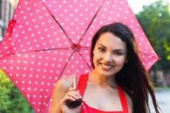 Portrait of beautiful young girl walking with umbrella Stock Image