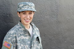 Portrait of beautiful young girl wearing green military style jacket and hat isolated on gray Stock Photography